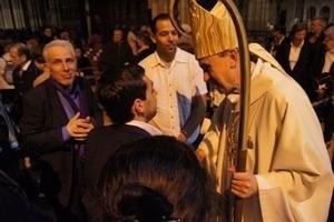 Des membres de la communauté rejoignent l'évêque après la bénédiction finale
