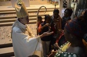 L'évêque bénit des membres de l'assemblée