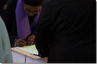 Doté de l'écharpe violette, chaque catéchumène va signer le registre...